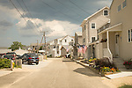 Shoreline street with crowded shorefront summer homes.