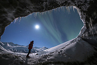 Man views the northern lights from inside a glacier ice cave in the Alaska Range mountains, Interior, Alaska.