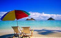Beach chairs under a multicolored umbrella on a tropical beach. seascape, islands on the horizon. Hawaii.
