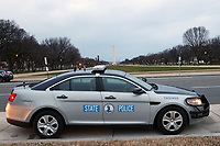 WASHINGTON, D.C. - JANUARY 8:  The Washington Monument stands in the background as State Police squad car is parked to prevent any further disturbances after a mob of Donald Trump supporters rushed the US Capitol 2 days prior. Washington, D.C. on January 8, 2021. <br /> CAP/MPI34<br /> ©MPI34/Capital Pictures