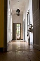 An open door from the corridor leads into a bedroom suite