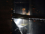 (Boston 04/30/16)  A Boston fire fighter looks at the partially collapsed rear porch from the second floor, as water pours down from above him,  Saturday, April 30, 2016, in Dorchester. The fire at 8 Montello Street heavily damaged the rear of the the triple decker home and melted the siding off the house next door. No one was reported injured but radio reports said 14 adults and 4 children were displaced by the fire.  Herald Photo by Jim Michaud
