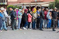 Marrakesh, Morocco.  Moroccans in a Line, Place Jemaa El Fna.