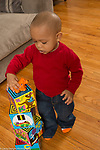 "18 month old toddler boy happy looking at toy he has put on top of tower of cardboard blocks, concept ""on top of"""