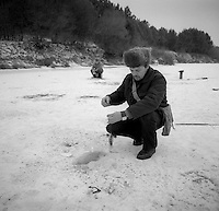Gomel, Belarus, Ocober 1995..The explosion at the Chernobyl Nuclear Power Plant on April 26 1986 was the worst nuclear accident in history..Fishing on a frozen river in the closed and radioactive zone surrounding Chernobyl..