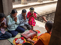 A local family receives their blessing by a Buddhist Monk at Angkor Way, Cambodia,