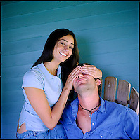 Woman, looking at camera, covering eyes of man sitting with her<br />