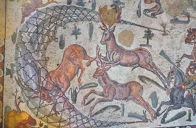 Close up detail picture of the Roman mosaics of the small hunt depicting deer being caught in a net trap, room no 24 at the Villa Romana del Casale, first quarter of the 4th century AD. Sicily, Italy. A UNESCO World Heritage Site.<br /> <br /> The Small Hunt room was used as a living room for guests of the Villa Romana del Casale. The Small hunt mosaic design has 4 registers running across the mosaic depicting hunting scenes. In the first register two servants are handling hunting dogs. In the second register figures are depicted burning incense at an altar to Diana, the goddess of hunting, before the hunt starts. The offering is being made by Constantius Clorus , the Caesar of Emperor Maximianus who owned the Villa Romana del Casale. Behind him is his son the future Emperor Constantine. To the right of the altar is a figure holding the reins of a horse dressed in a clavi decorated with ivy leaves indicating that he belongs to the family of Maximianus.