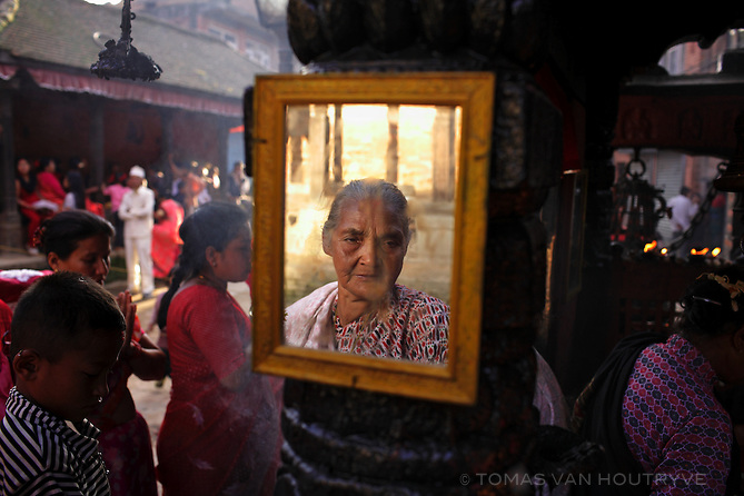 A Hindu women is reflected in a temple mirror on Maha Asthamithe, the ninth day of the Dashai festival in Bhaktapur, Nepal on 19 October, 2007. Dashai is the largest festival in Nepal, when Hindus offer sacrifices to Durga, the goddess of victory