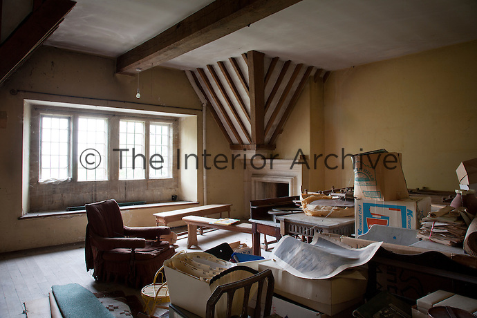 Cobwebs gather on the window, furniture and papers in this storage room