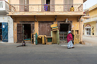 Senegal, Saint Louis.  Woman Walking Past Furniture Upholstery Shop.  Typical colonial era architecture: working shop on ground level, living quarters above.