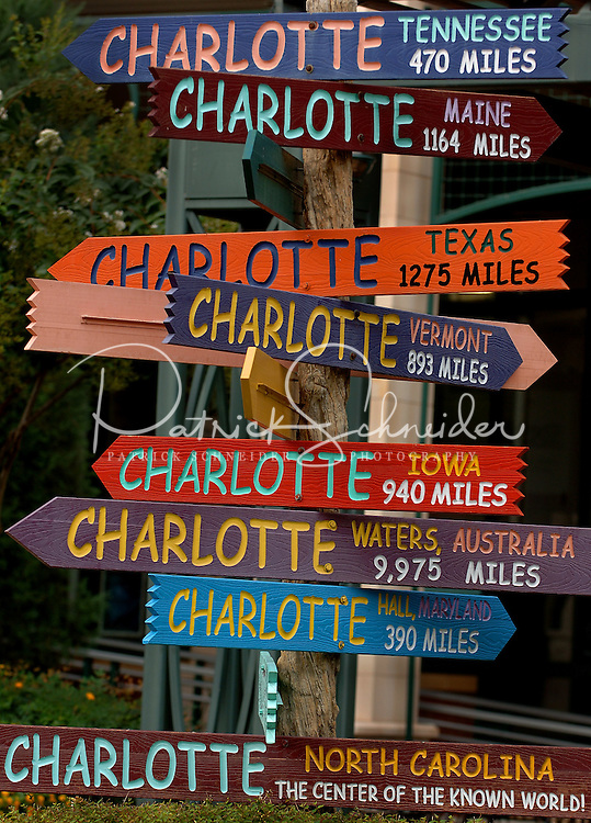 Colorful signs show mileage distances from Charlotte to other towns, states and countries at the Green park in uptown Charlotte, NC.
