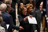 Former Defense Secretary Leon Panetta, left, greets former President George Bush, right, as he and his wife, former first lady Laura Bush follow the flag-draped casket of former President George H.W. Bush as it is carried out by a military honor guard during a State Funeral at the National Cathedral, Wednesday, Dec. 5, 2018, in Washington. Also pictured is Columba Bush, the wife of former Florida Gov. Jeb Bush, second from right. <br /> Credit: Andrew Harnik / Pool via CNP