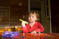 Baby boy holding plastic fork looking at camera