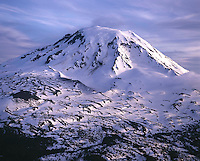 Aerial - medium shot of Mount Adams in sunset lighting, with 300 foot high lava vent cone in left foreground. Washington State.