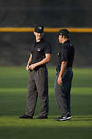 (L-R) Appalachian League umpires Trevor Matthews and Mickey Smith chat between innings of the playoff game between the Burlington Royals and the Pulaski Yankees at Calfee Park on September 1, 2019 in Pulaski, Virginia. The Royals defeated the Yankees 5-4 in 17 innings. (Brian Westerholt/Four Seam Images)