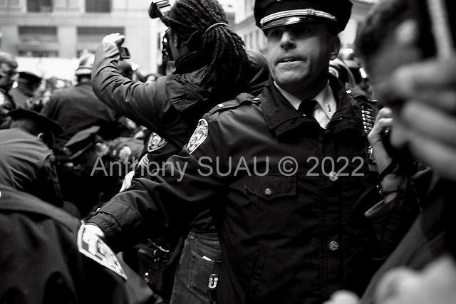 """New York, New York<br /> November 17, 2011<br /> <br /> """"Occupy Wall Street"""" protesters mark the movement's two-month milestone by marching from Zuccotti Park, in mass, to various access streets surrounding the New York Stock Exchange, which the police had barricaded off. Yet instead of the police keeping protesters out, protesters locked down those entrances to Wall Street and the New York Stock Exchange creating havoc as the police made more then 240 arrests to try and keep the streets open to normal traffic.<br /> <br /> At Williams Street and Exchange Place, just two blocks from the NYSE, a policeman tries to arrest a man in the crowd and contain a crowd of anti-Wall Street demonstrators from disrupting business as usual in the financial district. Dozens of arrests are made as protesters do battle with police."""