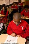 K-8 Parochial School Bronx New York Grade 4 children reading along in class boy using finger to point at workds vertical