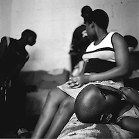 Ntando, lying on the bed, is a woman living in room in a shared house with a large number of tenants from Zimbabwe.