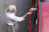 MEDELLÍN-COLOMBIA-16-08-2012. Una anciana indigente recibe una moneda de un conductor en la ciudad de Medellín./ Old homeless woman receives a coin from a driver in Medelín.   Photo: VizzorImage/Luis Benavides