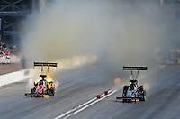 Mar. 31, 2012; Las Vegas, NV, USA: NHRA top fuel dragster driver Damien Harris (left) has an engine fire alongside Doug Kalitta during qualifying for the Summitracing.com Nationals at The Strip in Las Vegas. Mandatory Credit: Mark J. Rebilas-
