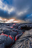 The sun sets behind glowing lava in the expansive fields of Hawai'i Volcanoes National Park, Hawai'i Island.