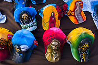 Colorful baseball caps, featuring various Santa Muerte (Holy Death) pictures, are being sold on the street during a religious pilgrimage in Tepito, Mexico City, Mexico, 1 April 2018. The religious cult of Santa Muerte is a fusion of Aztec death worship rituals and Catholic beliefs. Born in lower-class neighborhoods of Mexico City, it has always been closely associated with crime. In the past decades, original Santa Muerte followers, such as prostitutes, pickpockets and street drug traffickers, have merged with thousands of ordinary Mexican Catholics. The Holy Death veneration, offering a spiritual way out of hardship in modern society, rapidly expanded. Although the Catholic Church still considers Santa Muerte followers the devil worshippers, on the first day of every month, crowds of Santa Muerte believers fill the streets of Tepito. Holding statues of Holy Death clothed in a long robe, they pray for healing, protection, money or any other favor in life.