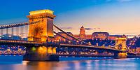 Iconic Szechenyi Chain bridge lit up at twilight, with the historic Royal Palace Buda castle and Danube River reflection, Budapest Hungary