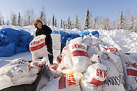 """February 16, 2013  Volunteer Jennifer Ambrose piles musher food bags bound for Skwentna and which will be loaded into volunteer Iditarod Air Force planes at the Willow Airport during day one of the """"Food Fly""""...Photo Copyright Jeff Schultz  -- Do not reproduce without written permission"""
