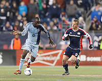 Sporting Kansas City midfielder Lawrence Olum (13) brings the ball forward.  In the first game of two-game aggregate total goals Major League Soccer (MLS) Eastern Conference Semifinal series, New England Revolution (dark blue) vs Sporting Kansas City (light blue), 2-1, at Gillette Stadium on November 2, 2013.