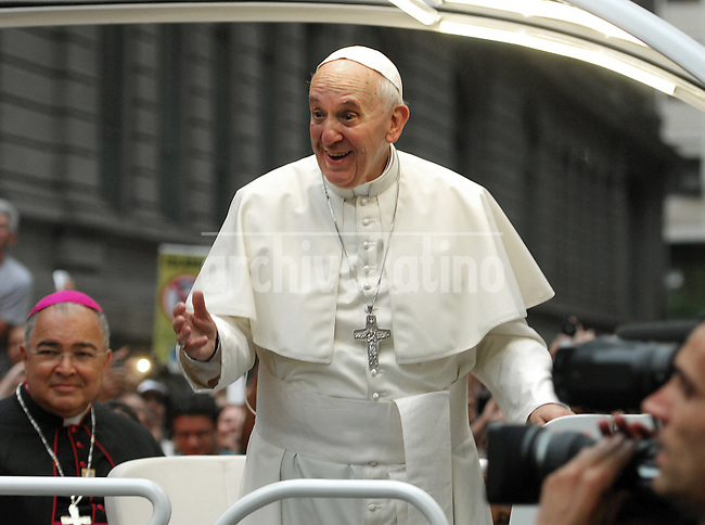 Pope Francis waves from his popemobile as he makes his way from Cathedral to downtown of Rio de Janeiro, Brazil, July 22, 2013. The pontiff arrived for a seven-day visit in Brazil and to participate at church's World Youth Day festival meeting legions of young Roman Catholics. (Austral Foto/Carlos Junior)
