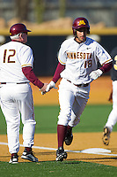 Justin Gominsky #18 of the Minnesota Golden Gophers shakes hands with head coach John Anderson as he rounds third base to score a run against the Towson Tigers at Gene Hooks Field on February 26, 2011 in Winston-Salem, North Carolina.  The Gophers defeated the Tigers 6-4.  Photo by Brian Westerholt / Sports On Film