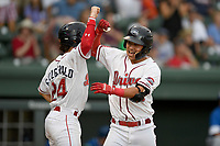 Third baseman Tanner Nishioka (30) of the Greenville Drive is congratulated by Ryan Fitzgerald (24) after hitting a three-run home run during a game against the Lexington Legends on Sunday, September 2, 2018, at Fluor Field at the West End in Greenville, South Carolina. Greenville won, 7-4. (Tom Priddy/Four Seam Images)