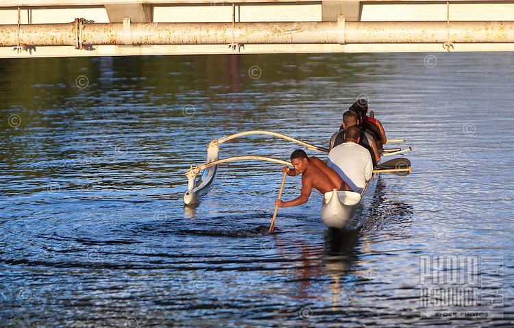 Local men paddling a canoe on Anahulu River under the bridge in Haleiwa, O'ahu.
