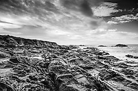 The Pacific coast, gouged by tafoni formations and cast in black and white.  Bean Hollow State Beach near Pescadero, south of San Francisco, on California's coast.