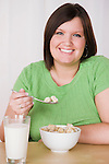 Portrait of smiling young woman eating healthy breakfast