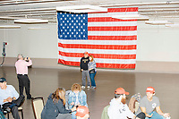 People pose for pictures with a giant American flag before Donald Trump, Jr., the son of US president Donald Trump, speaks at a 'Make America Great Again!' campaign rally at DoubleTree by Hilton MHT in Manchester, New Hampshire, on Thu., Oct. 29, 2020. The event took place five days before the Nov. 3 presidential election.