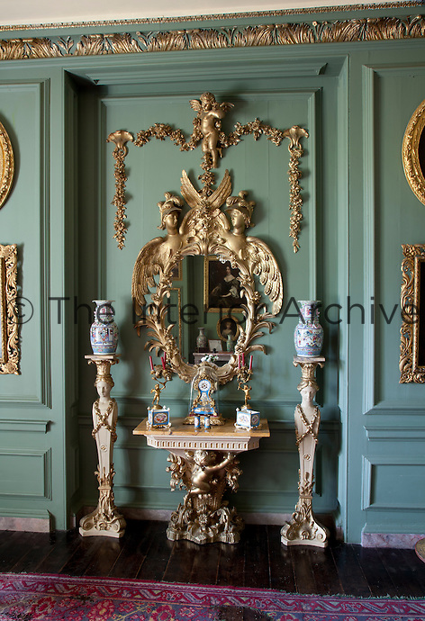 An elaborately carved and gilded mirror flanked by two vases on Grecian pedestals in the Grenville Room