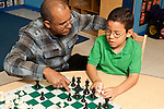 Afterschool chess program for elementary students graduates of Headstart program male teacher working with child