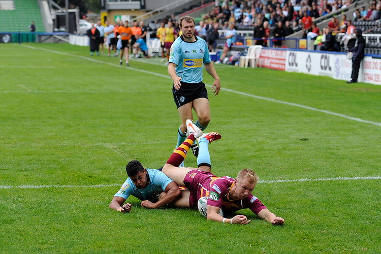 Aaron Murphy of Huddersfield Giants dives over to score a try despite the efforts of Kieran Dixon of London Broncos during the Super League match between Huddersfield Giants and London Broncos at The Twickenham Stoop on Saturday 17th August 2013 (Photo by Rob Munro)