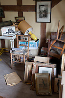 Stacks of pictures and broken furniture in a storage room