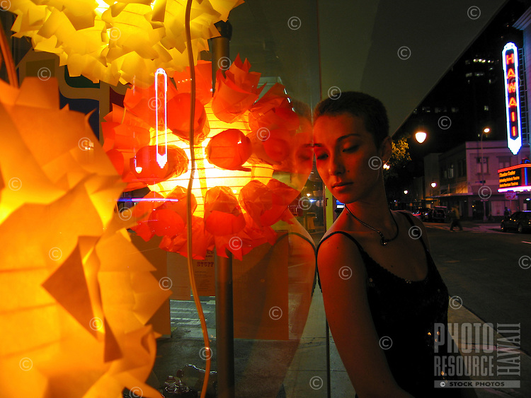 A young woman leans against the window of a shop featuring brightly colored lamps, with the Hawai'i Theatre in the background, Chinatown, O'ahu.
