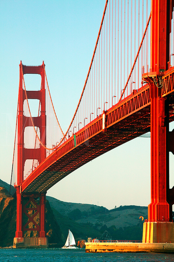 A sailboat passes under the Golden Gate Bridge in the evening from the Presidio, San Francisco, California