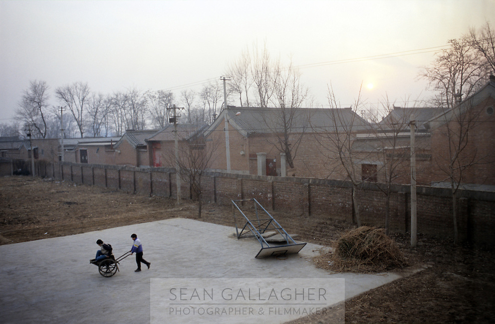 CHINA. Beijing. Orphans outside an orphanage outside of Beijing. 2007. The orphanage is a mix of orphans and children left for long periods of time by migrant workers who cannot take their children with them. There are currently millions of orphans in China living in orphanages spread throughout the country. As a result of China's one-child policy, many children are abandoned or given up if they suffer from any physical or mental handicap as the parents strive to have a child born 'normal' and well. This has led to may children being abandoned to live in state and privately-owned orphanages.