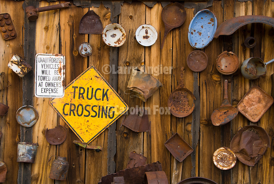 Rusting tools, pans, artifacts of a ghost town displayed on the wall of the town's saloon