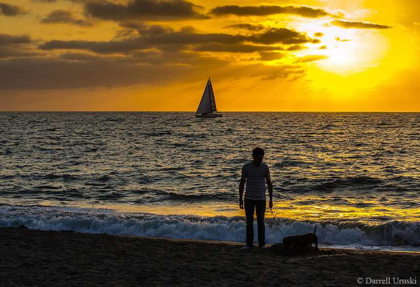 Fine Art Print Photograph, Sunset Walking the dog in Banderas Bay, Puerto Vallarta, Mexico. Sailboat passes by the setting sun.