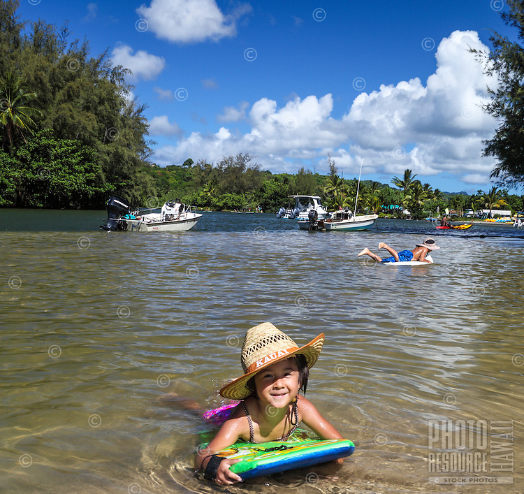 A girl wearing a straw hat plays on a boogie board in shallow water as her brother maneuvers on a boogie board in the deeper waters of Hanalei River, Kaua'i.