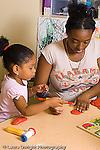 Preschool parent volunteer working with girl art activity play dough vertical