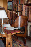 An unusual walnut chair in the small library. Antique, leather bound books fill the shelves of the bookcase behind it