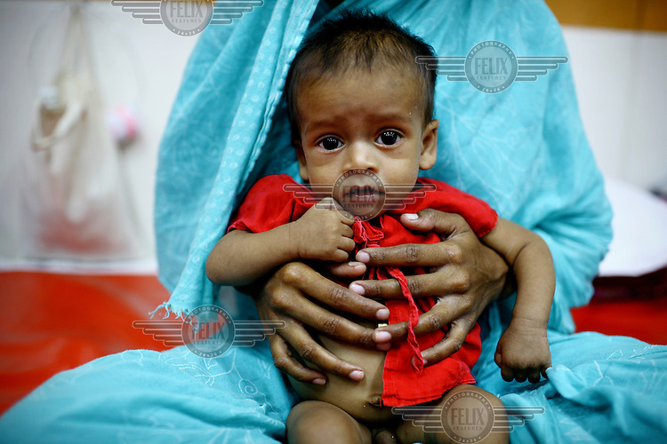 A mother holds her baby on her lap. The baby is receiving treatment for diarrhoea at the International Centre for Diarrhoea Disease Research, Bangladesh (ICDDR B). The ICDDR is an international health research organization established in 1978 and credited with discovering oral dehydration therapy for the treatment of diarrhoea and cholera.